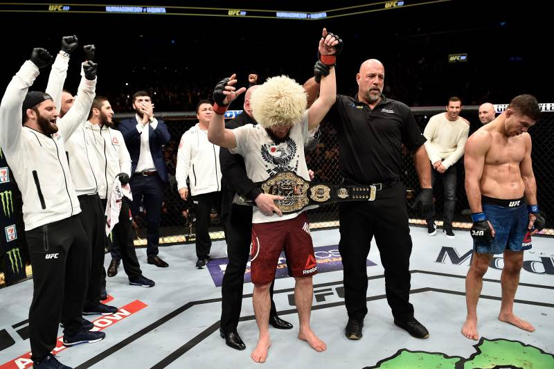 Khabib with hands raised as belt is wrapped around his waist.